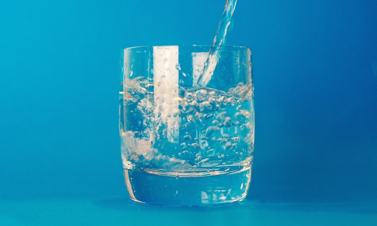 A stream of water being poured into a clear glass of water against a blue background