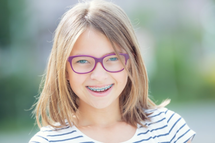 Young girl with braces and purple glasses smiles as she learns about the special training her orthodontist received