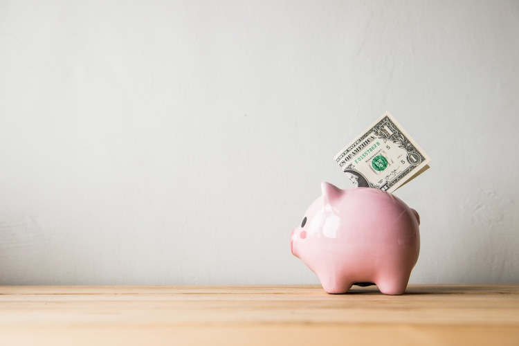 A pink piggy bank with a dollar bill sticking out of it sits on a wooden counter against a white wall