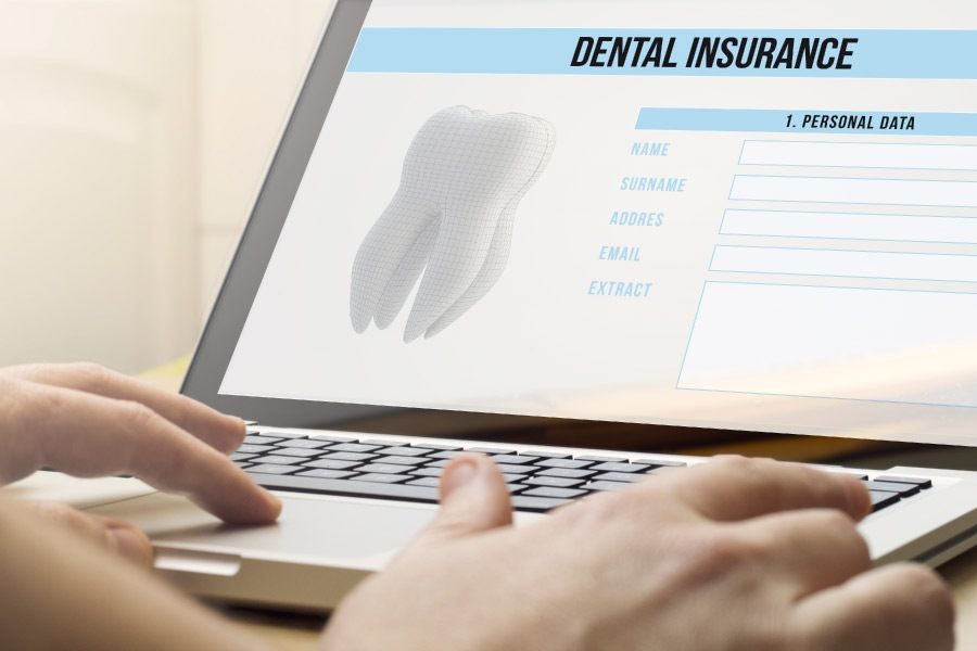Hand typing on a computer screen showing dental insurance information.