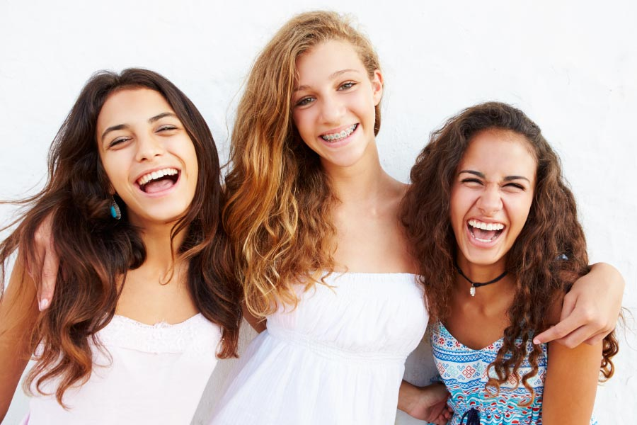 Three lovely teenage girls laughing with the middle one wearing braces.