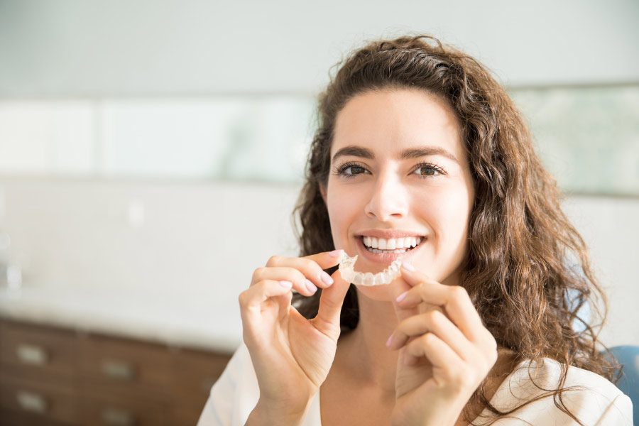 Brown haired smiling woman holding an Invisalign clear aligner in front of her teeth.